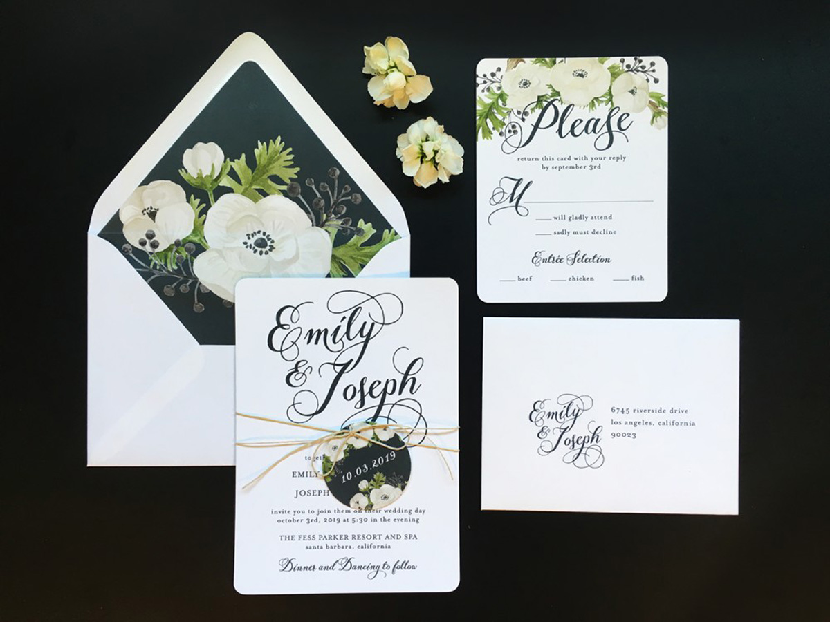 wedding invitation wrapped with floral tag