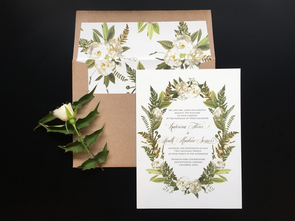 wedding invitation with wreath of greenery and white flowers