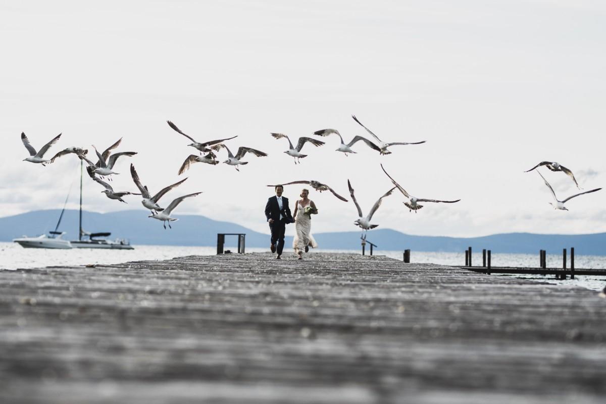 Jeramie Lu Photography - Lake Tahoe wedding couple running on dock with seagulls