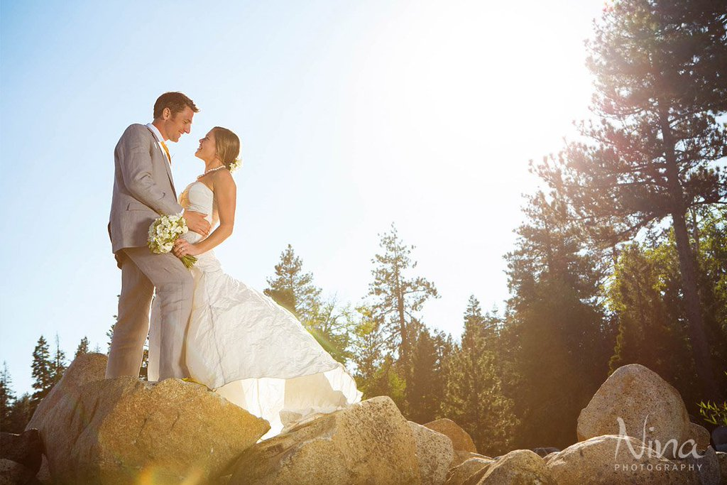 Couple on rocks near water and trees Lake Tahoe wedding