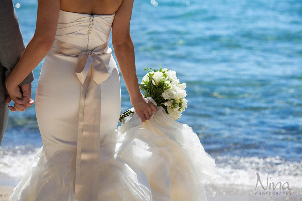 Bride with bouquet on Lake Tahoe beach wedding