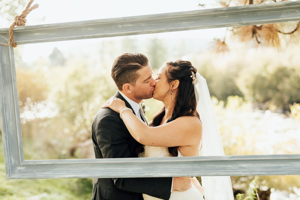 Truckee River Lake Tahoe wedding couple kissing by picture frame