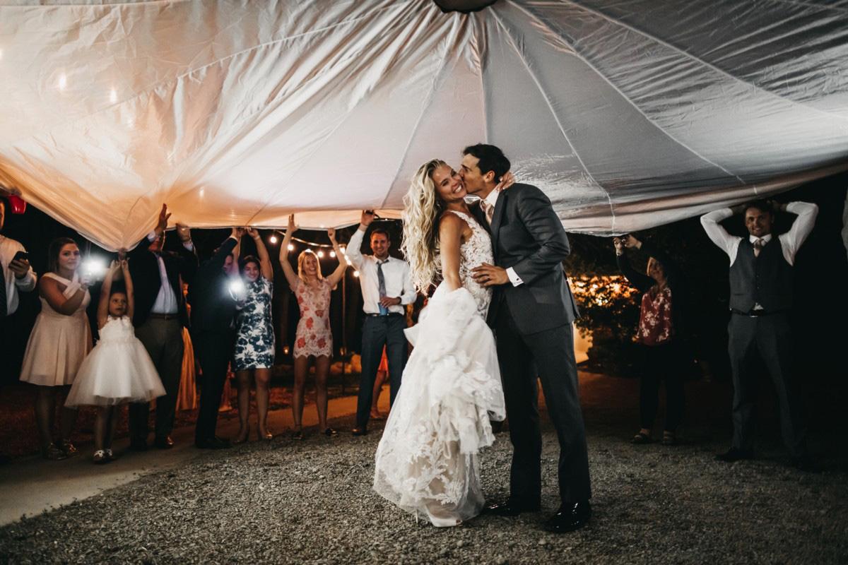 Wedding at The Hideout - VILD Photography - couple under send-off parachute