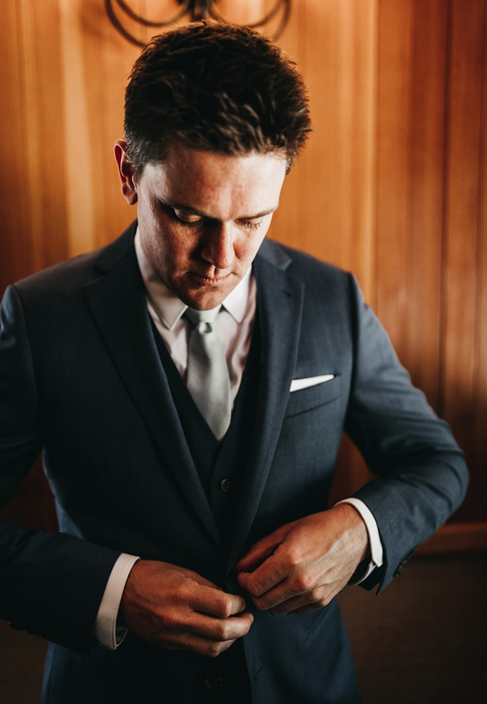 rustic relaxed wedding Lake Tahoe - groom buttoning coat