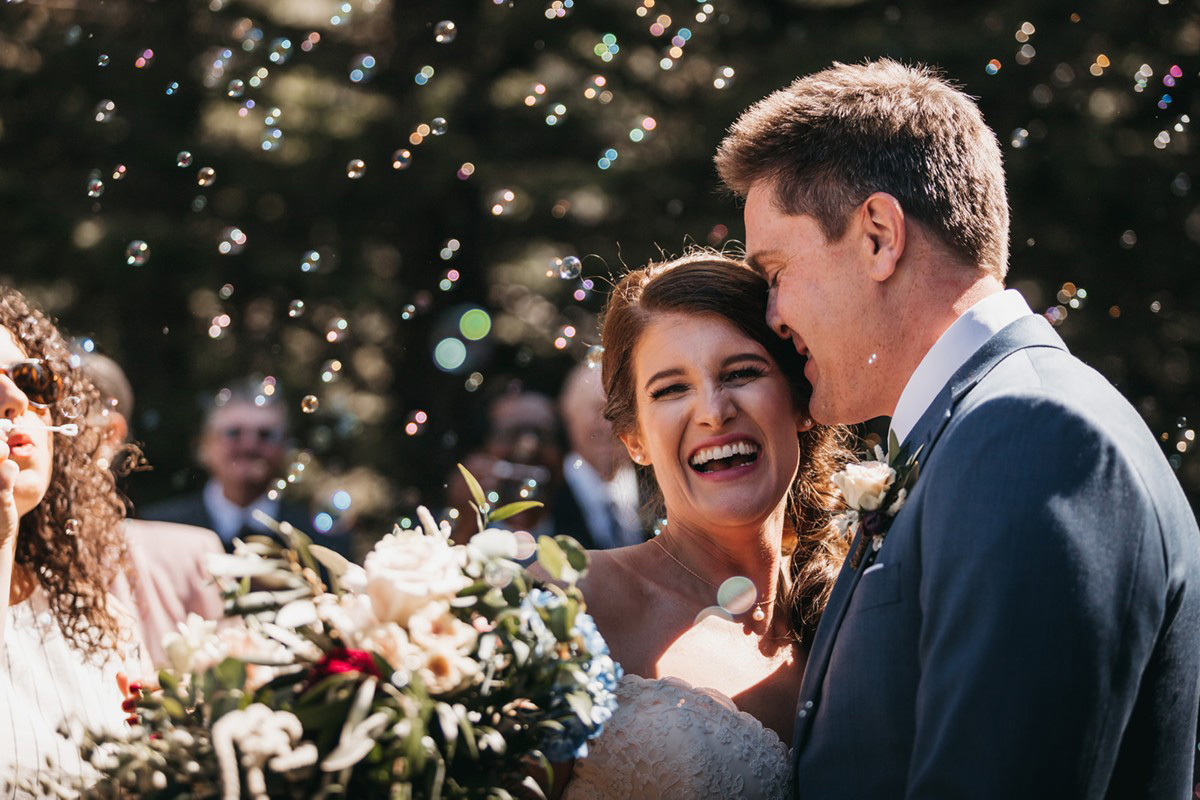 rustic relaxed wedding Lake Tahoe - couple just married with bubbles blowing in air