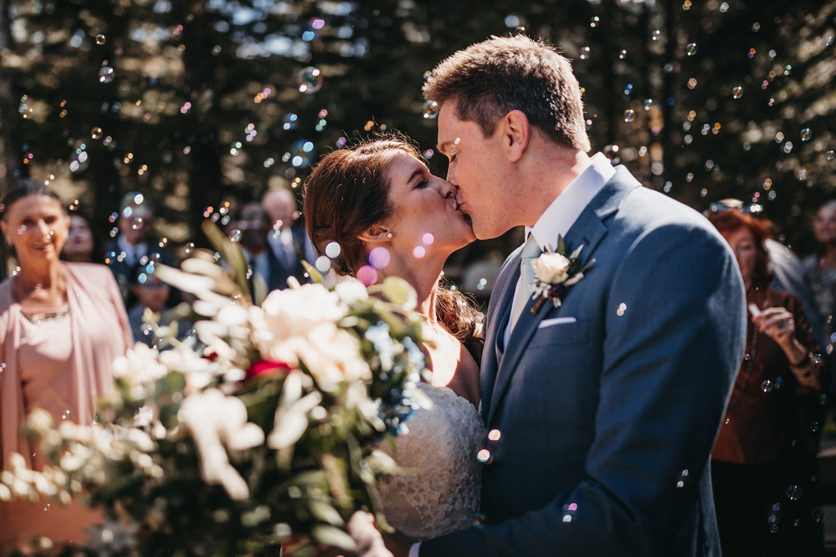 rustic relaxed wedding Lake Tahoe - couple kissing with bubbles in air