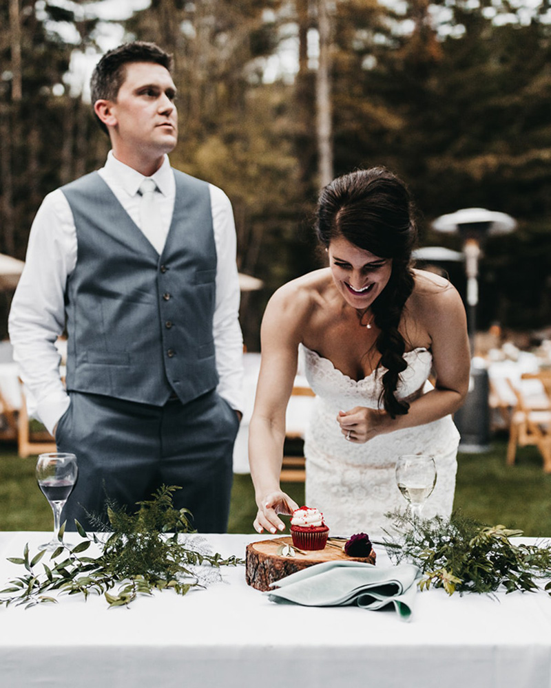 rustic relaxed wedding Lake Tahoe - bride cuts the cupcake