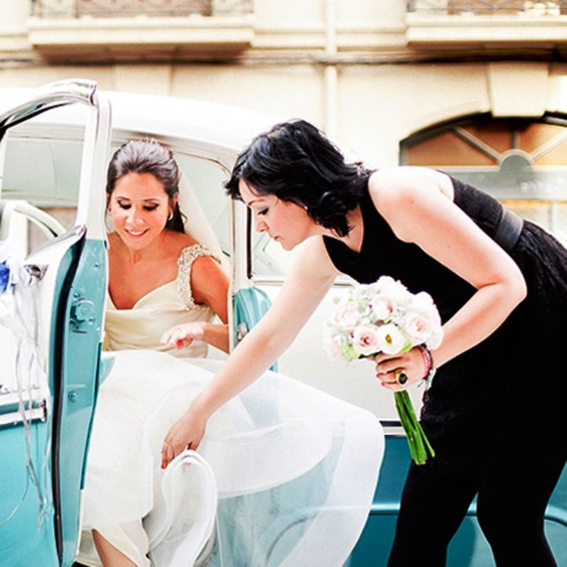 wedding planner helping bride out of limousine