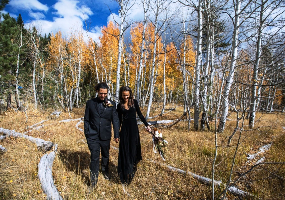 couple eloped to Lake Tahoe walking near forest with fall foliage
