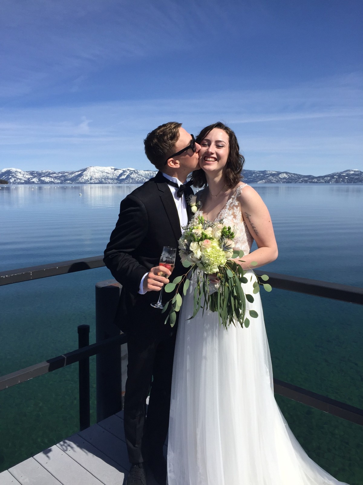 eloping couple kissing at end of Lake Tahoe pier