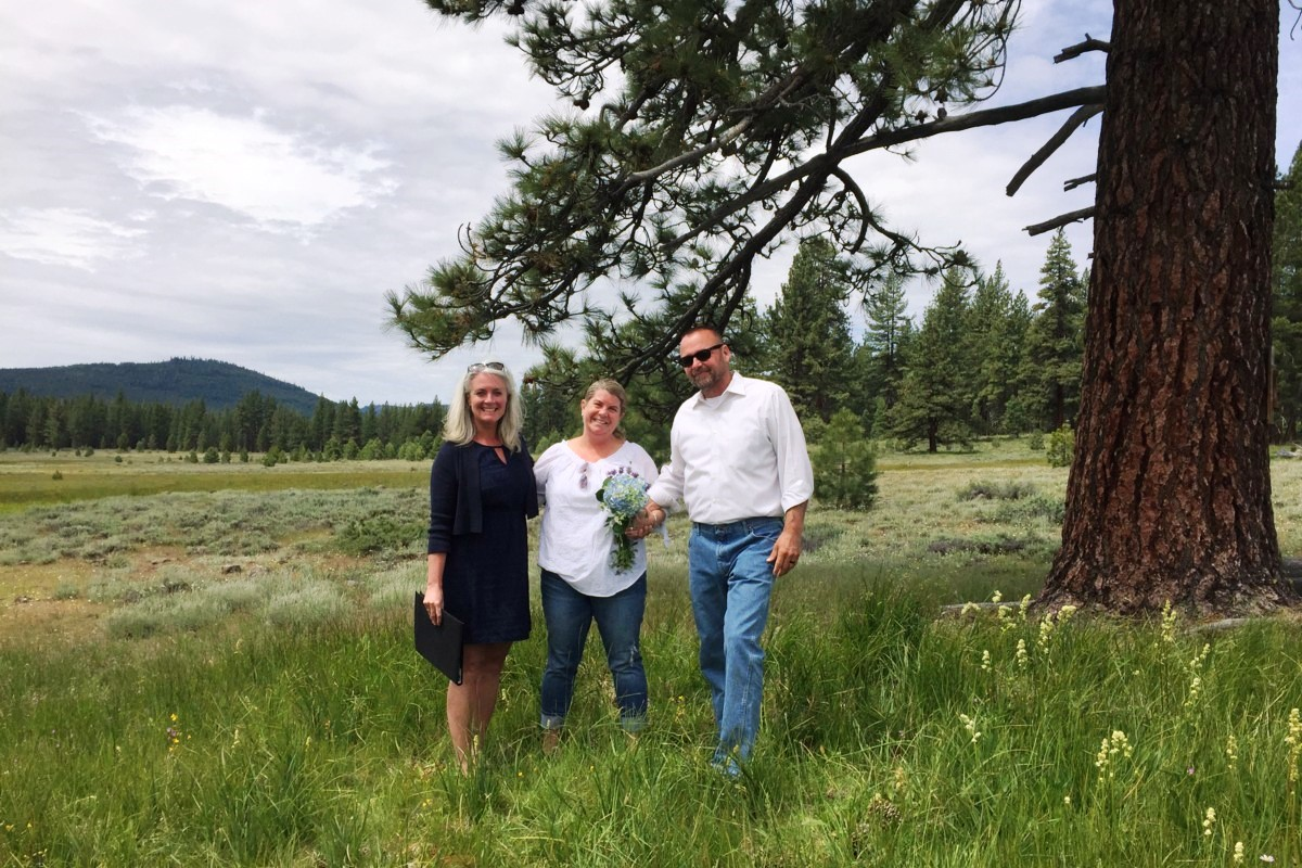 couple with officiant under pine tree at intimate location near Lake Tahoe