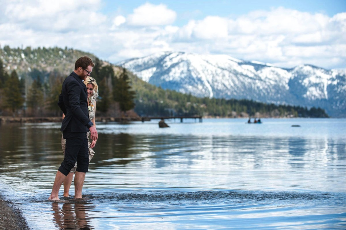 couple walking in Lake Tahoe water with winter snow on mountains nearby