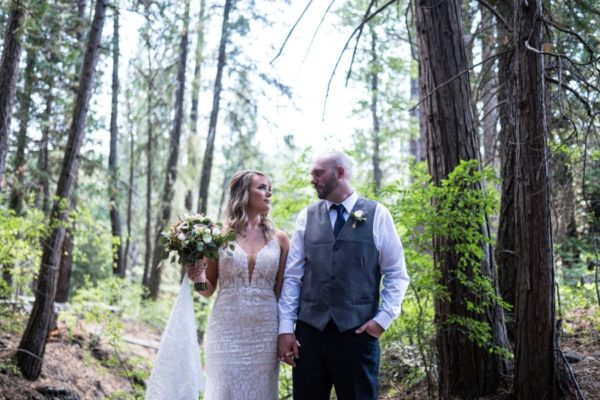Couple walking in forest after wedding ceremony